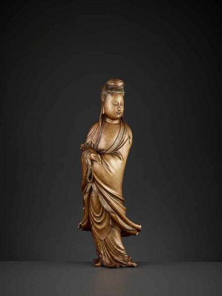 A LARGE BOXWOOD FIGURE OF GUANYIN China, 19th century. Carved standing and dressed [...]