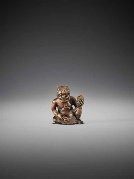A WOOD SHUNGA NETSUKE OF AN ONI WITH CLAM