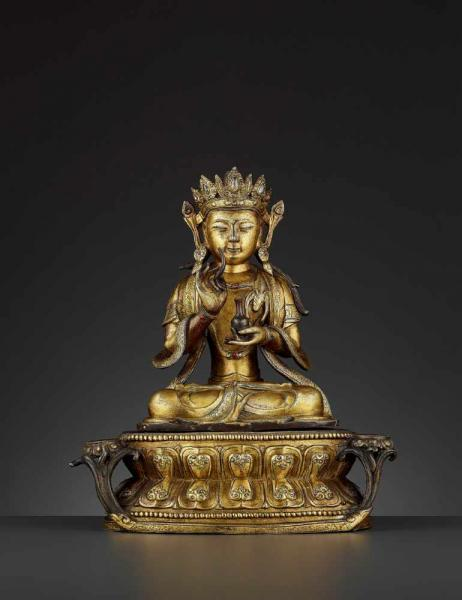 A LARGE FIRE-GILT BRONZE AVALOKITESHVARA, MING China, 1368-1644. The Boshisattva is [...]