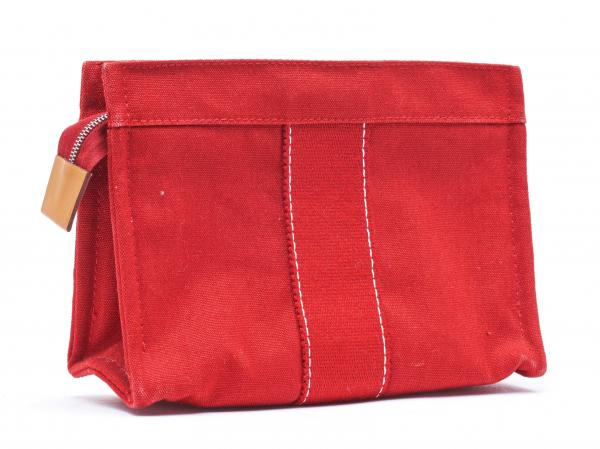 HERMÈS PARIS  -   - A TOILETRY CASE in red canvas, white stitching. Silver-tone [...]