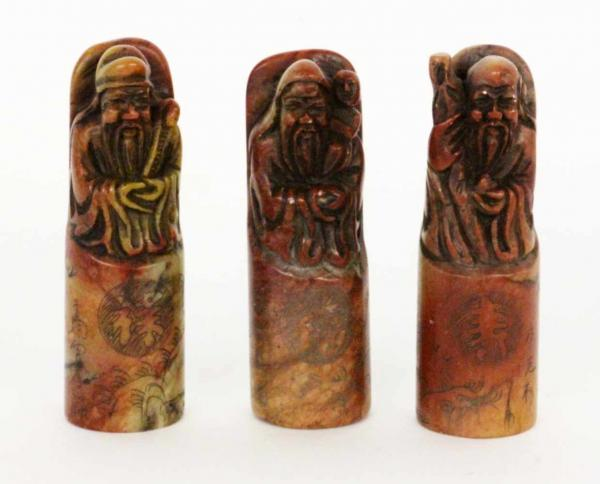 ''THREE FIGURES OF GODS China. Probably red marble. Cut figures and engraved decoration.