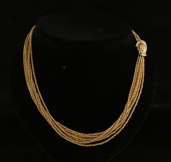 Collier ras de cou 7 rangs en or jaune noué et matifié. Fermoir en or blanc serti [...]