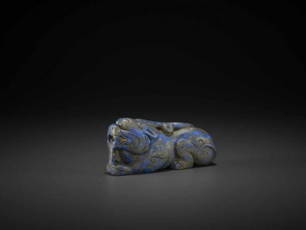 A LAPIS LAZULI CARVING OF A LION DOG, QING China, 18th-19th century. In recumbent [...]