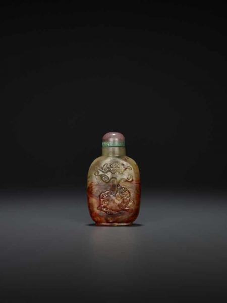 A RED JADE SNUFF BOTTLE China, 1740-1820. The stone finely carved and incised in high [...]